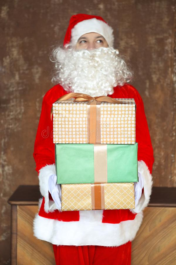 Santa Claus secretly putting gift boxes under the Christmas tree royalty free stock image