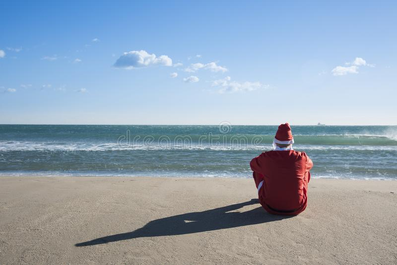 Santa claus sitting on the sand of a beach. Santa claus, seen from behind, sitting on the sand of a beach facing the sea, looking at the horizon stock images