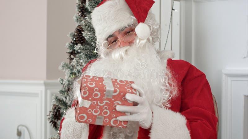 Santa Claus in seinen unterzeichnenden Geschenken der Weihnachtswerkstatt für Kinder stockfoto