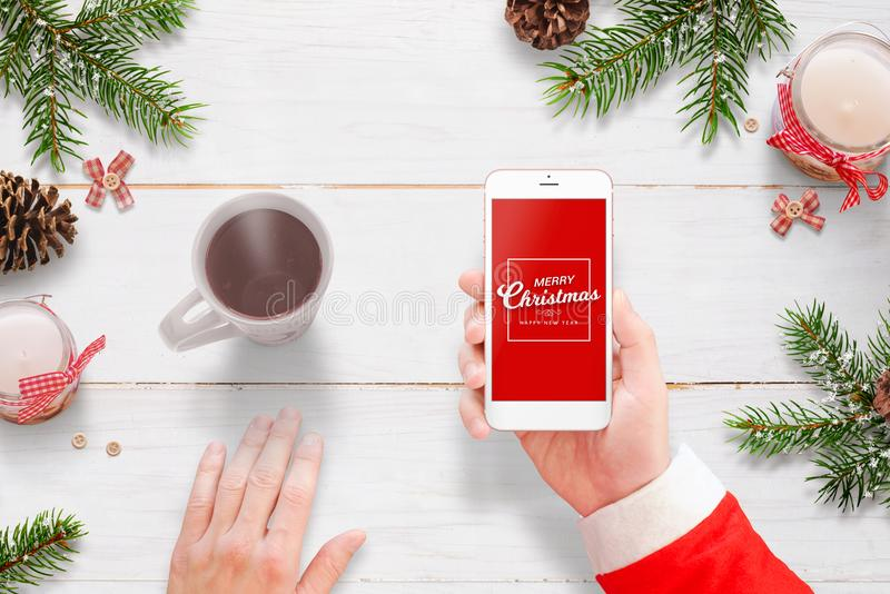 Santa Claus send Merry Christmas message with mobile phone. Hot tea, and Christmas decoration beside stock image
