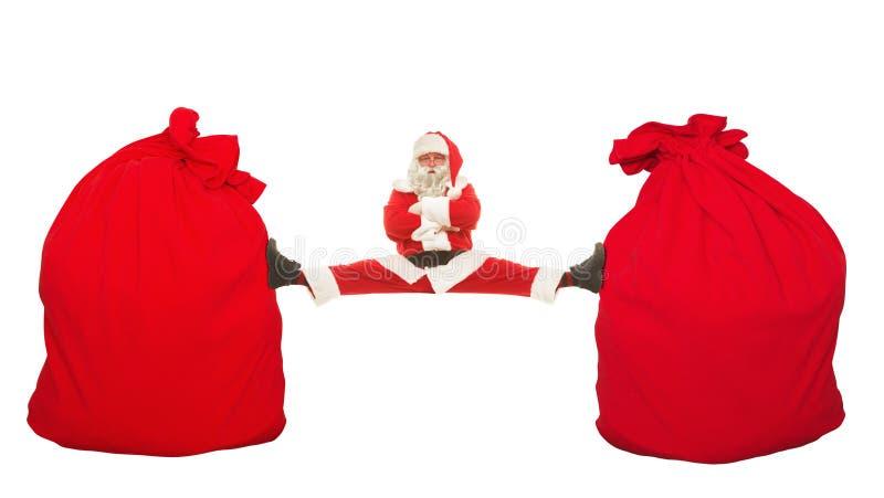 Santa Claus senta nas separações que esticam entre o saco de dois mbolshih imagens de stock royalty free