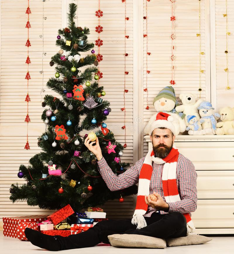Santa Claus with serious face wooden wall with garlands. And Christmas tree background. Festivals and decor concept. Man with beard holds golden Christmas balls royalty free stock photography