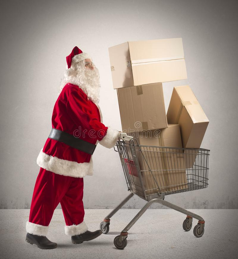 Santa Claus with shopping cart. Full of packages stock photography