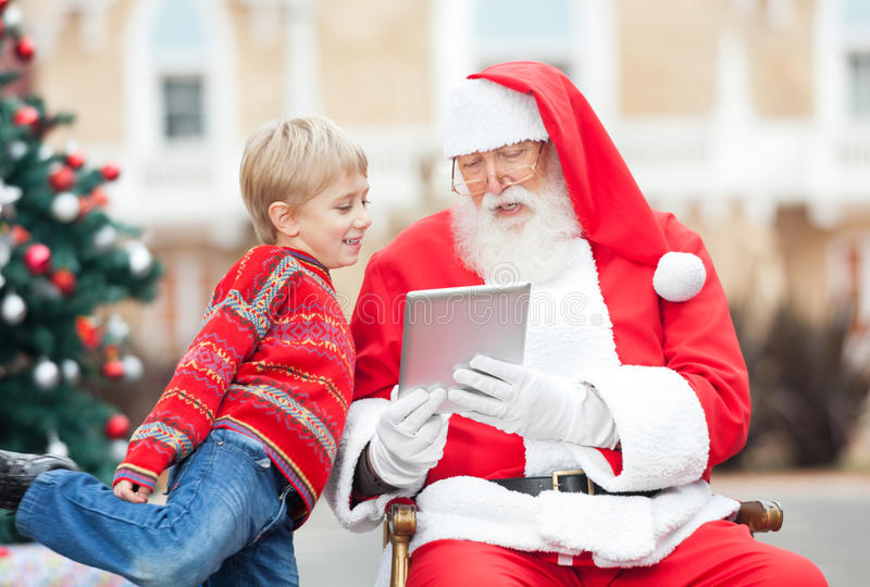 Santa Claus Showing Digital Tablet To Boy. In courtyard stock images