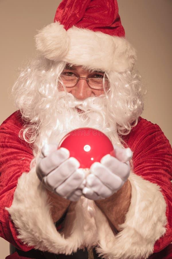 Santa Claus showing a red christmas ball. royalty free stock photos