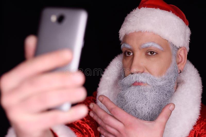 Santa Claus si prende alla macchina fotografica di uno smartphone immagini stock libere da diritti
