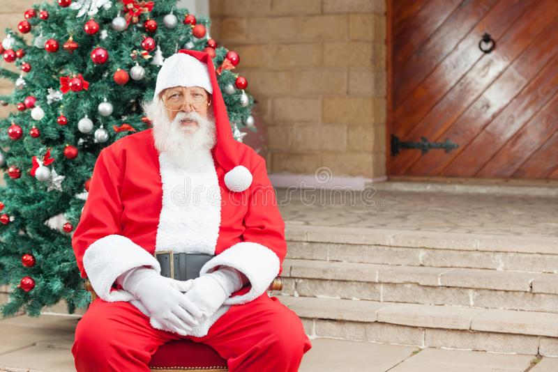 Santa Claus Sitting Against Christmas Tree arkivbilder