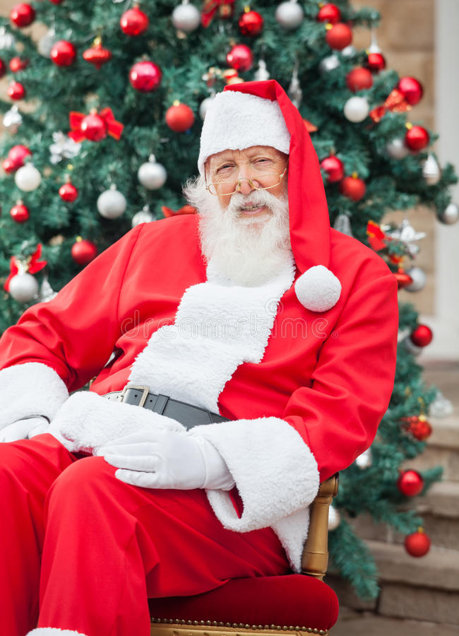 Santa Claus Sitting Against Decorated Christmas immagine stock