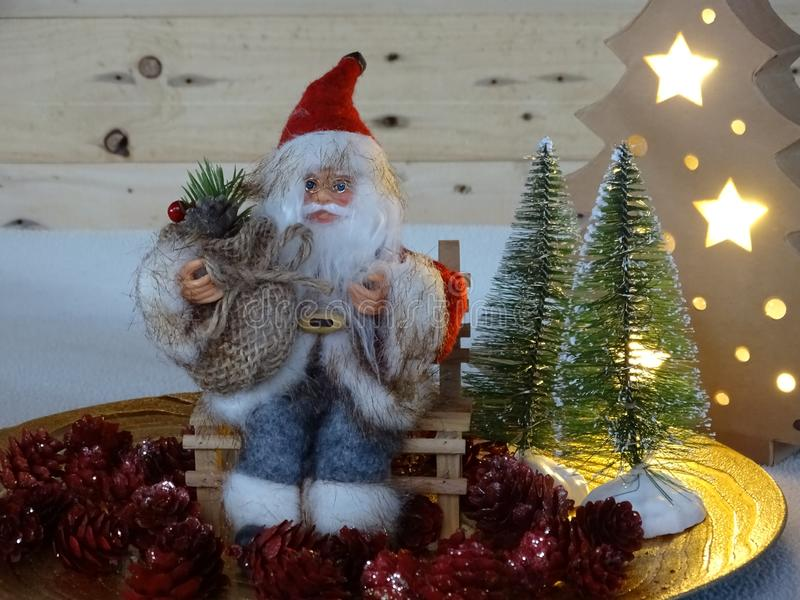 Santa claus sitting on a bank surrounded bij trees and pineappels. Santa claus sitting on a bank surrounded bij tree and red pineapples stock image