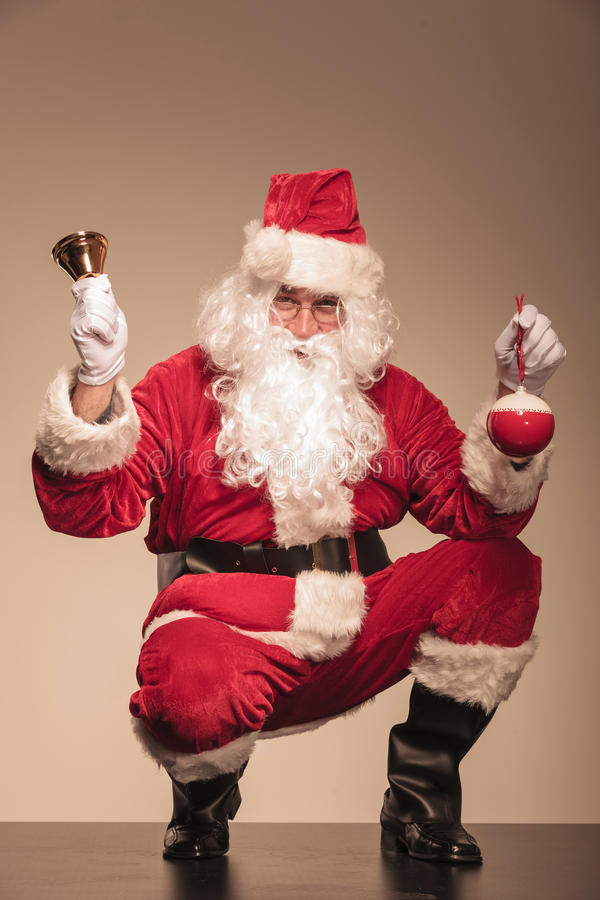 Santa CLaus sitting with a bell in his left hand stock photos