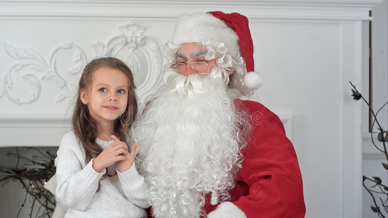 Santa Claus sitting in a chair with a little girl dreaming about her Christmas presents stock photos