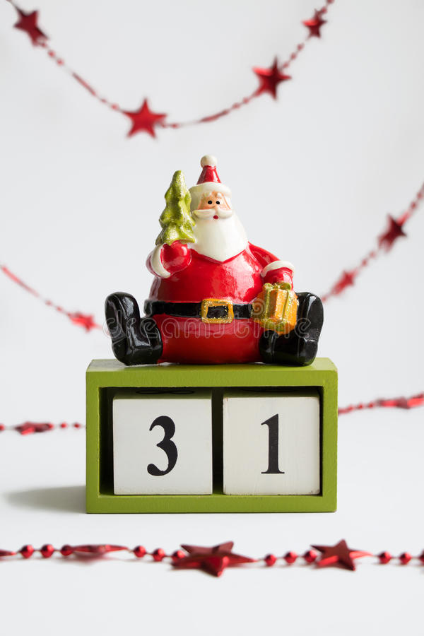 Santa claus sitting on cubes showing the date thirty first on white background with red garland. Symbolizing end of the year. Save the date calendar stock photo