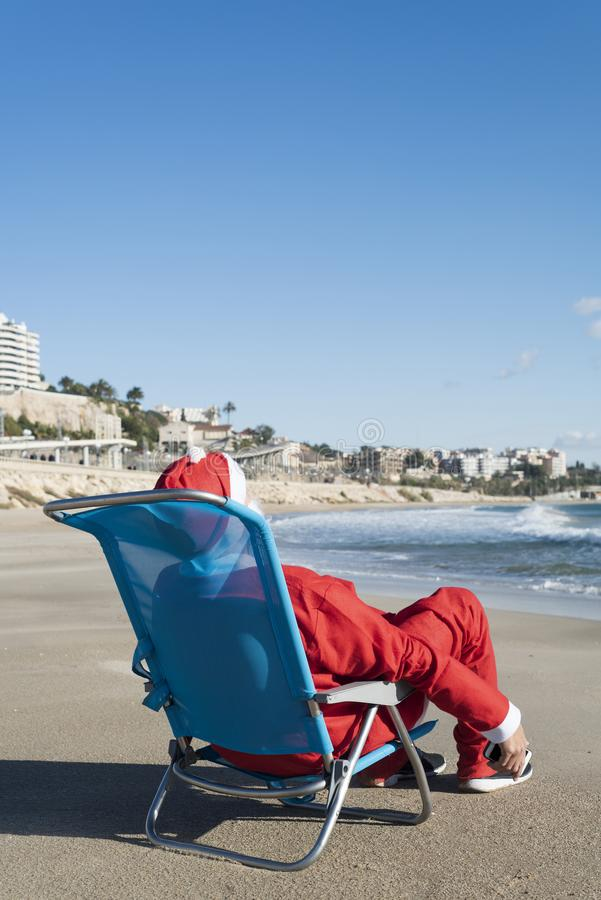 Santa claus sitting in a deckchair on the beach. Santa claus, seen from behind, sitting in a deckchair on the beach with a smartphone in his hand stock photos