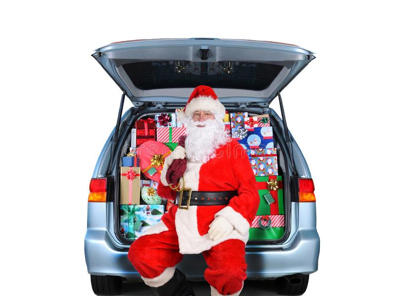 Santa Claus sitting in a Minivan with its rear door open and stuffed full with wrapped Christmas presents. Isolated on white stock photo