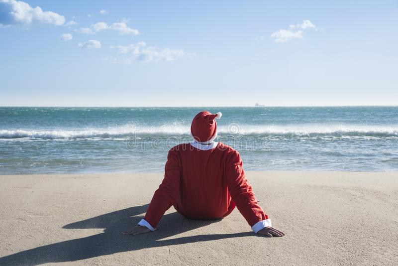 Santa claus sitting on the sand of a beach. Santa claus, seen from behind, sitting on the sand of a beach facing the sea, looking at the horizon stock photo