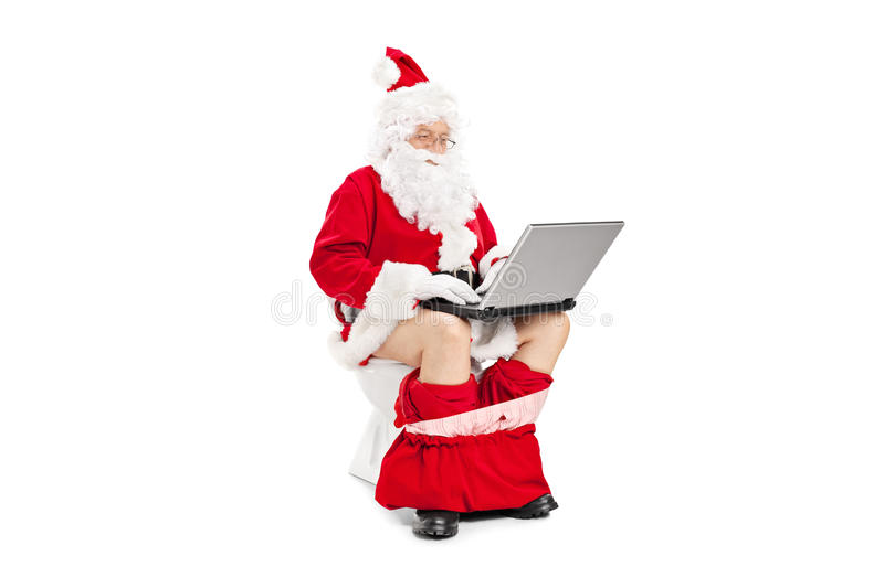 Santa Claus sitting on a toilet and working with laptop stock photos