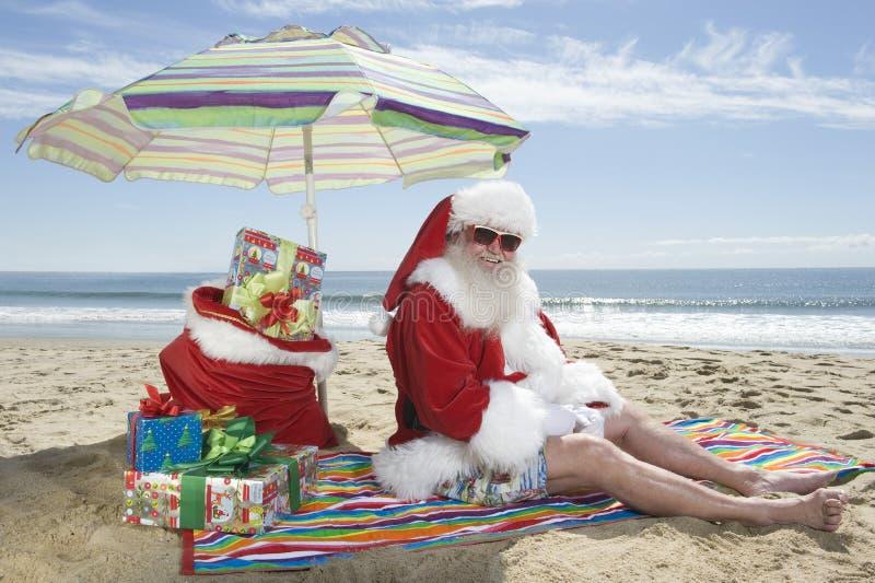 Santa Claus Sitting Under Parasol With gåvor på stranden arkivbilder