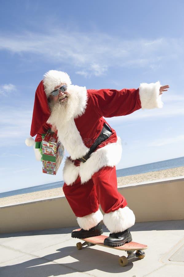 Santa Claus Skateboarding With Gift In-Hand royalty-vrije stock afbeeldingen