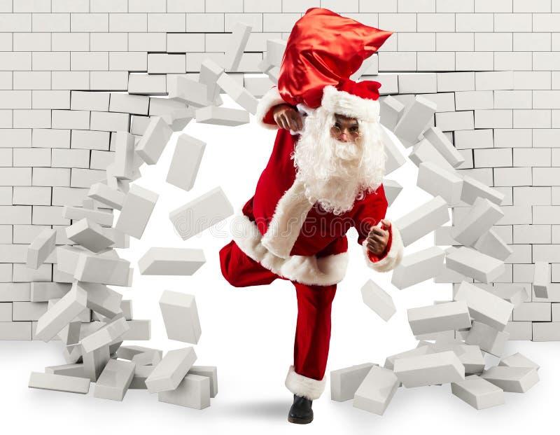 Santa Claus skriver in för att leverera gåvan, genom att göra ett hål i väggen royaltyfri fotografi