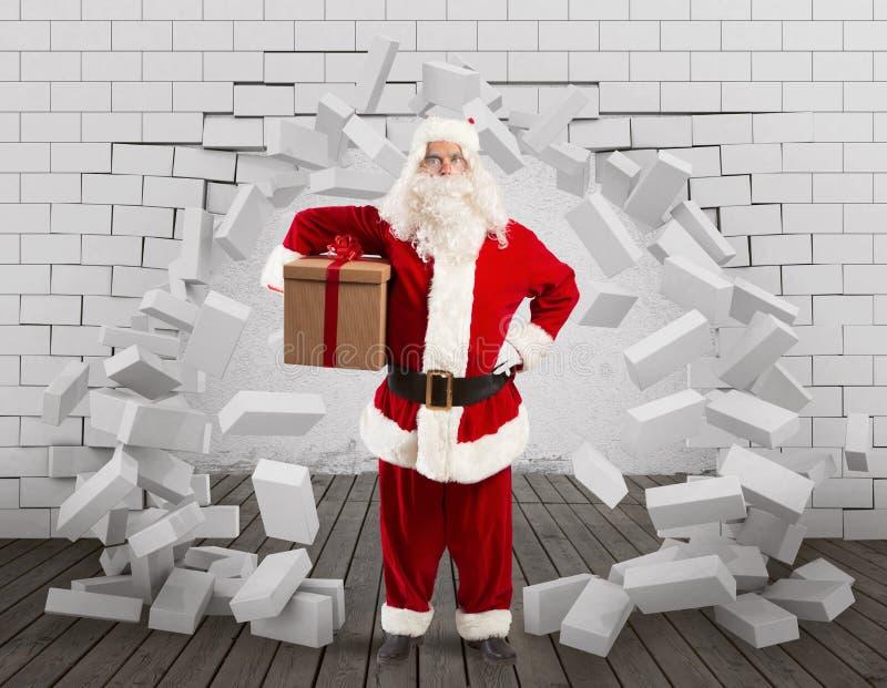 Santa Claus skriver in för att leverera gåvan, genom att göra ett hål i väggen royaltyfria bilder