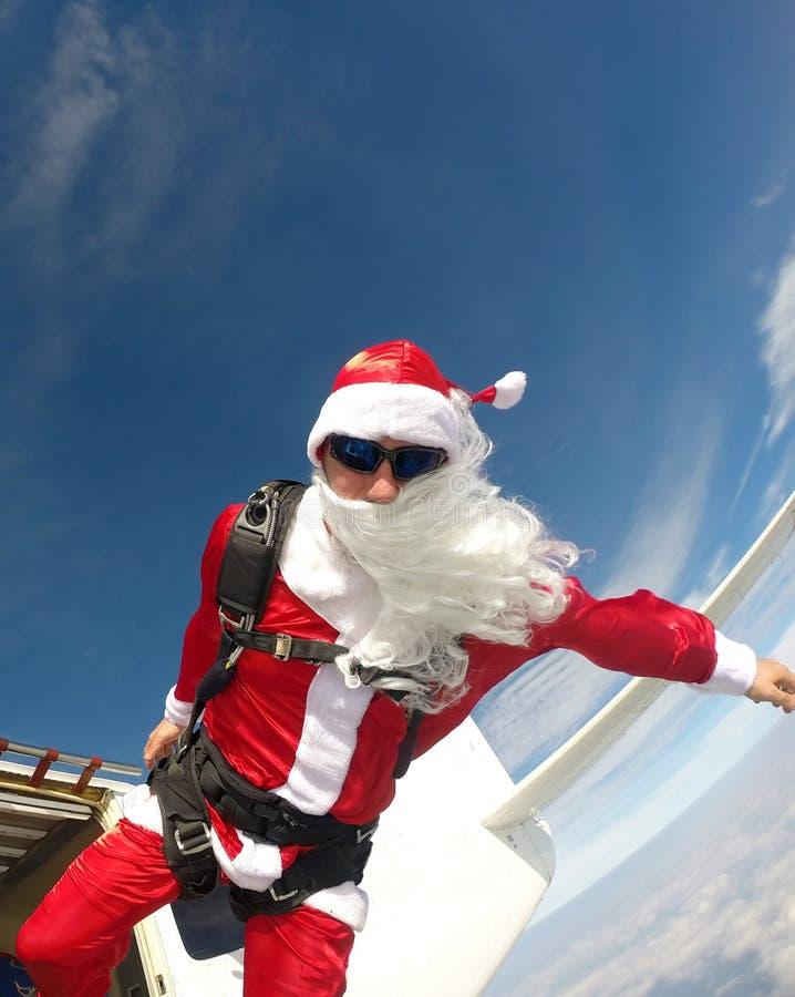 Santa Claus Skydiver salta do plano fotografia de stock