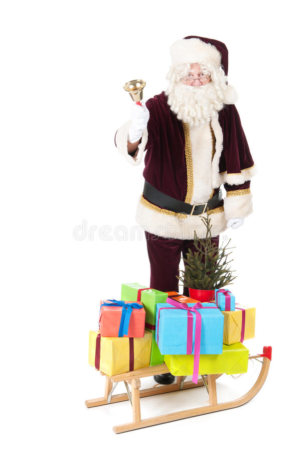 Santa Claus and sled with many Chirstmas presents. Sled with many colorful Christmas presents and tree pulled by Santa Claus isolated overwhite background royalty free stock images