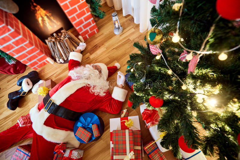 Santa Claus is sleeping, tired, drunk in a room near the fireplace and the Christmas tree after the New Year, Christmas. royalty free stock photography