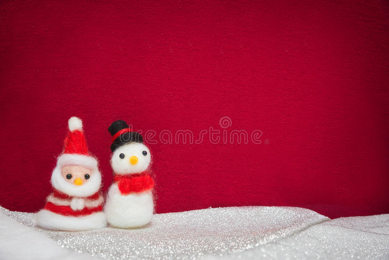 Santa claus, snowman wool doll on snow set up with red cloth backdrop, happy new year and christmas concept background with copy. Space royalty free stock images