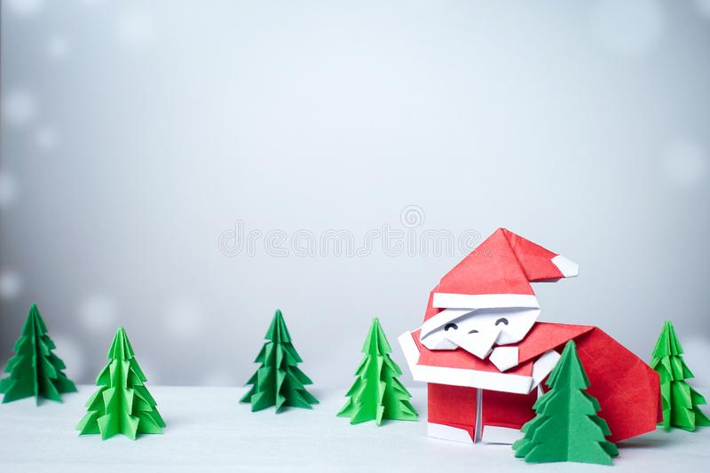 Santa claus in snowy winter background with paper cut christmas stock image