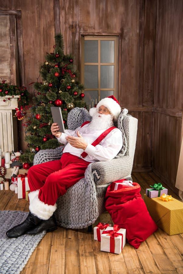 Santa Claus som använder den digitala minnestavlan royaltyfri foto