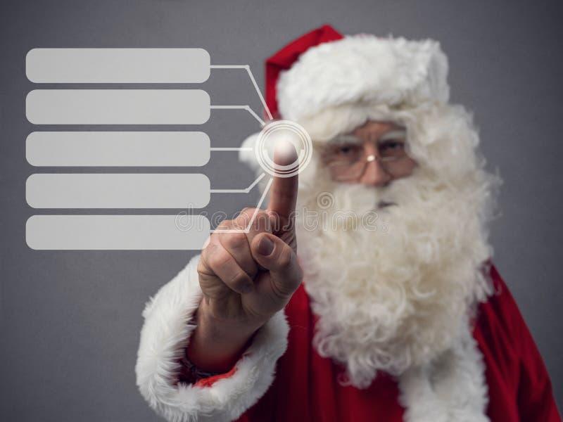 Santa Claus som använder en pekskärmanvändargränssnitt royaltyfria bilder