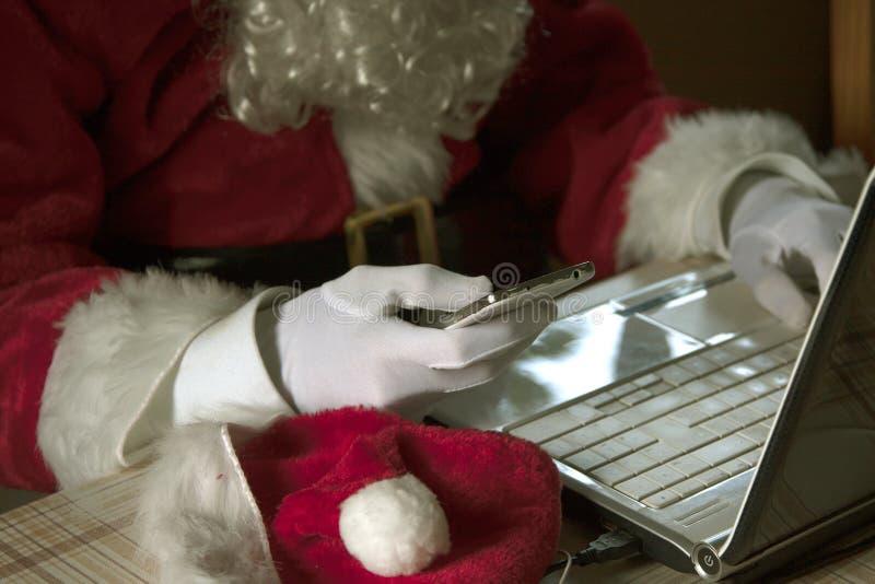 Santa Claus som använder smartphonen och bärbara datorn arkivfoton