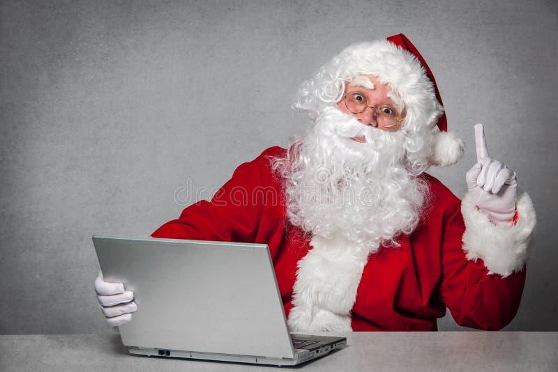 Santa Claus som arbetar med bärbara datorn arkivfoton
