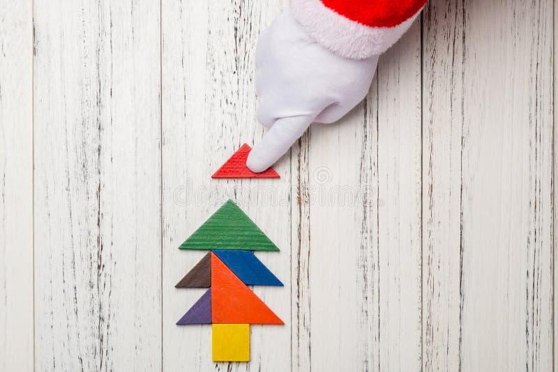 Santa Claus som avslutar den sista biten av julgranen som göras av den wood tangramen royaltyfri fotografi