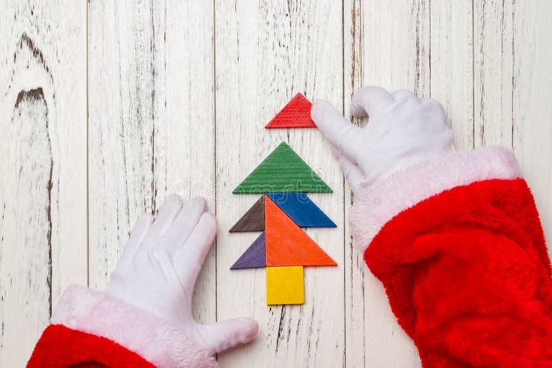 Santa Claus som avslutar den sista biten av julgranen som göras av den wood tangramen fotografering för bildbyråer