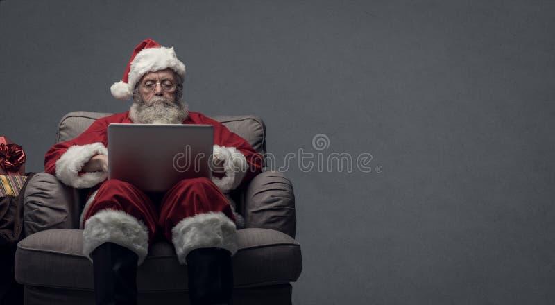 Santa Claus som förbinder med en bärbar dator arkivbilder