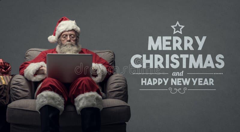 Santa Claus som förbinder med en bärbar dator royaltyfri foto