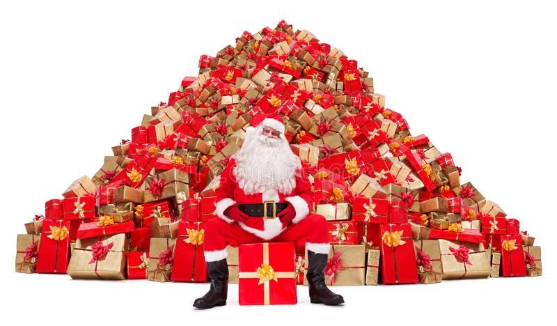 Santa Claus som framme sitter av en hög av julgåvor royaltyfri fotografi