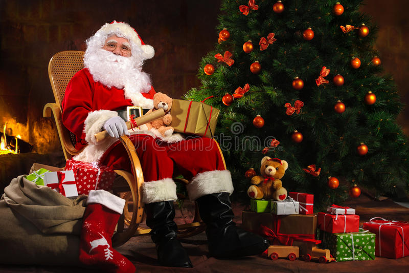 Santa Claus som framme sitter av spisen royaltyfria bilder
