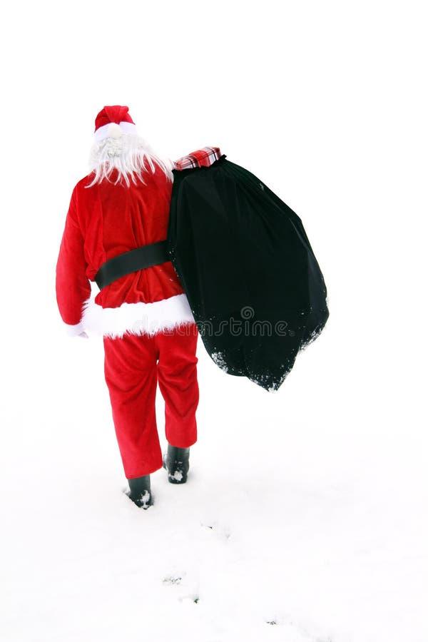 Santa Claus som går i snön arkivbild
