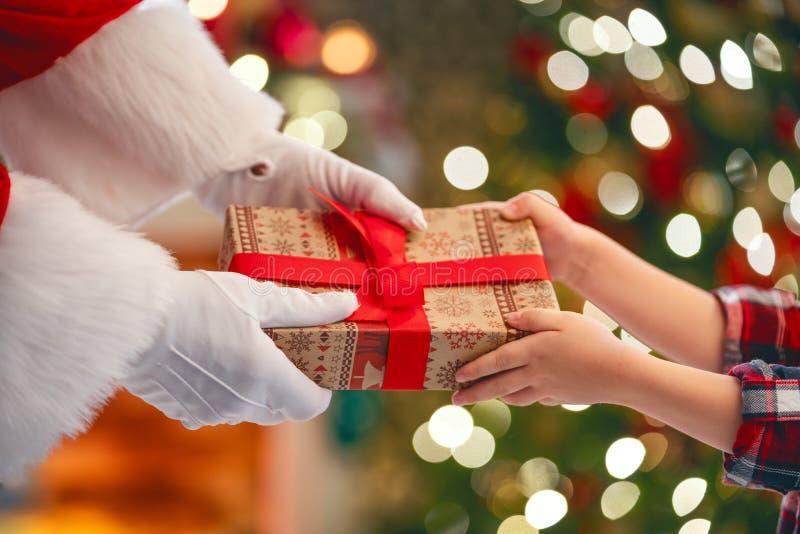 Santa Claus som ger gåvan till barnet arkivbilder