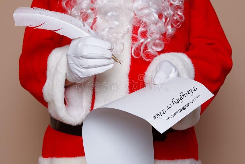 Santa Claus som kontrollerar hans lista royaltyfria bilder