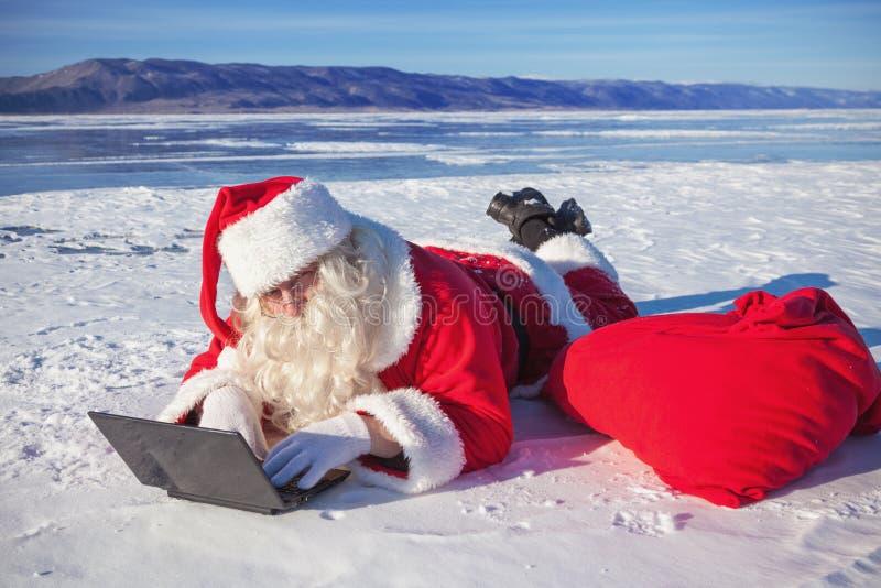 Santa Claus som ligger på snön som ser bärbar datornyheterna royaltyfri foto