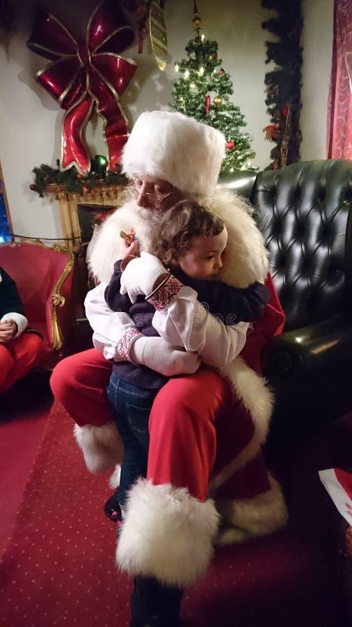 Santa Claus som lite kramar flickan royaltyfria bilder