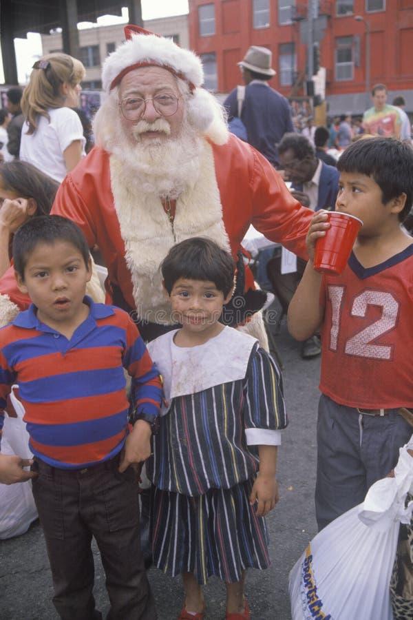 Santa Claus som poserar med hemlösa barn på julmatställen, Los Angeles, Kalifornien arkivfoto