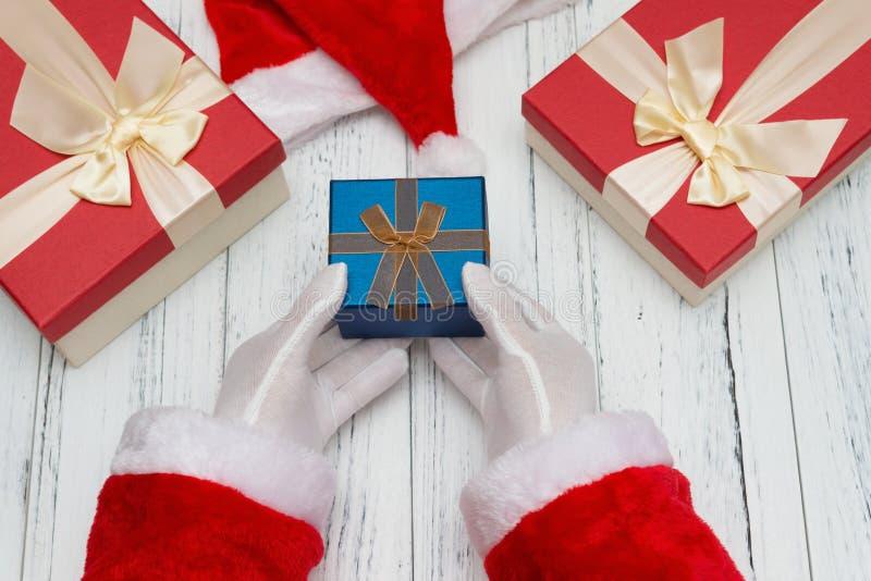 Santa Claus som räcker en julgåvaask med den närliggande hatten royaltyfria foton