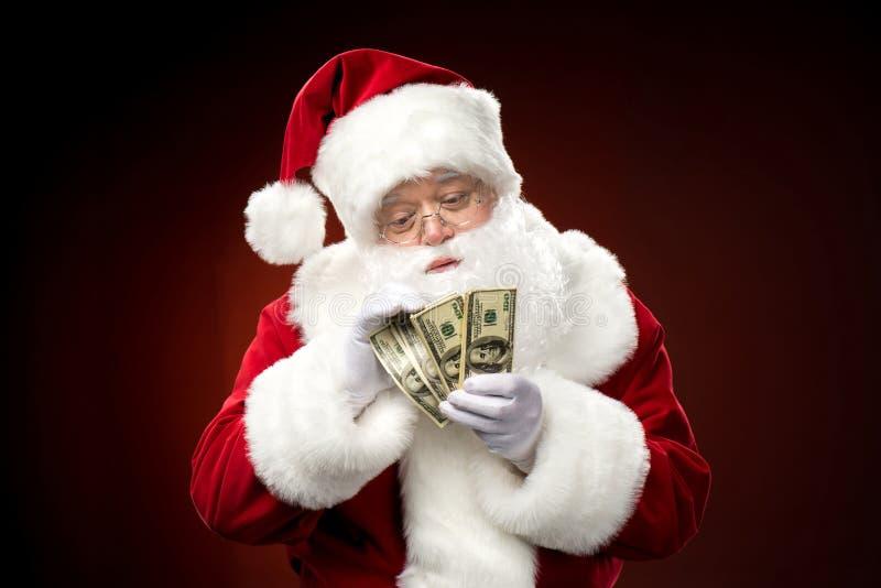 Santa Claus som räknar dollarsedlar royaltyfria foton