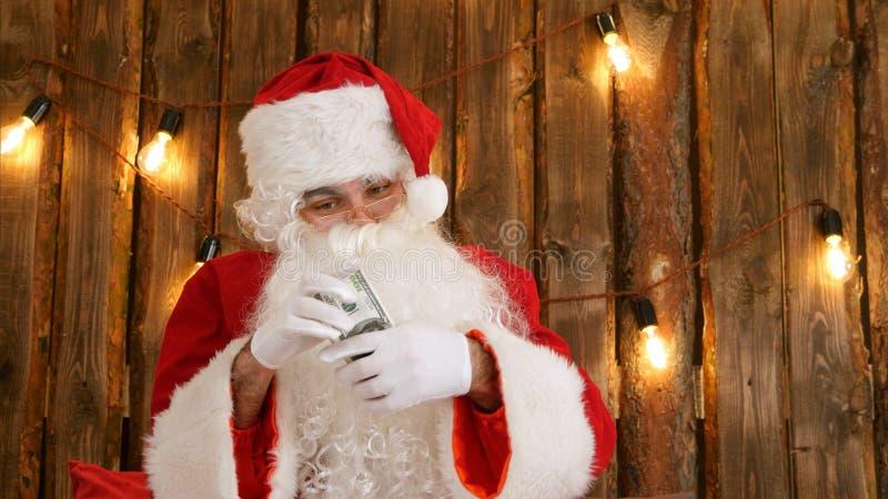 Santa Claus som räknar hans pengar och visar försvinnande trick för pengar arkivfoto
