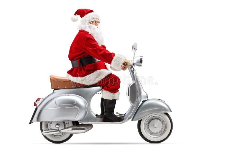 Santa Claus som rider en retro sparkcykel royaltyfria bilder