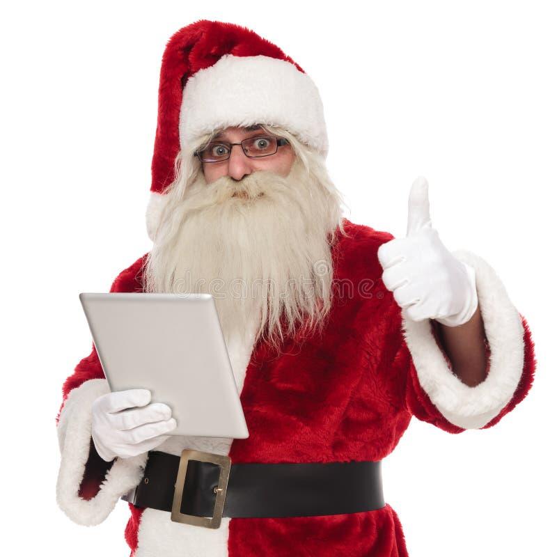 Santa Claus som rymmer den gråa minnestavlan, gör tummar upp tecken arkivbild